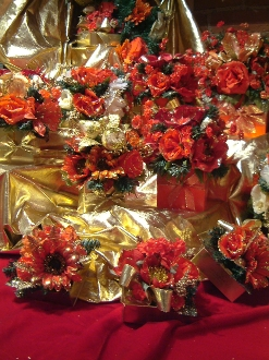 Image shows an arrangement of various sizes of gold holiday gift boxes with shiny gold, red and orange flowers on a red velvet cloth.