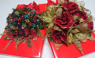 Images shows two bright red holiday luxury assortment boxes with shiny, opulent flowers on top, on a white background.