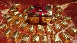 Image shows an array of gold-wrapped Marron Glacés on a red background.